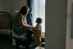 natural light photograph of mum getting daughter dressed at home