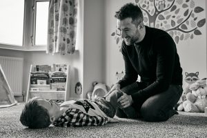Dad laughs and plays with son during natural family photoshoot