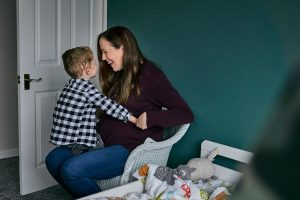 pregnant mum laughs with son at home in Cheshire