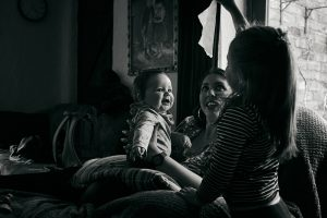 baby boy smiles at big sister during day in the life shoot