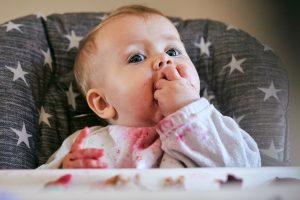 baby girl gets messy feeding herself during photoshoot