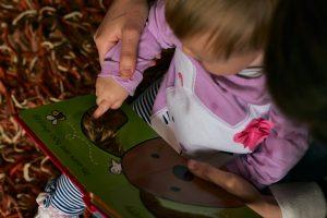 mum helps girl feel a baby book