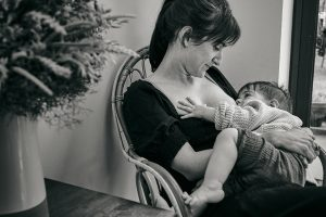 documentary photo of mum breastfeeding older girl