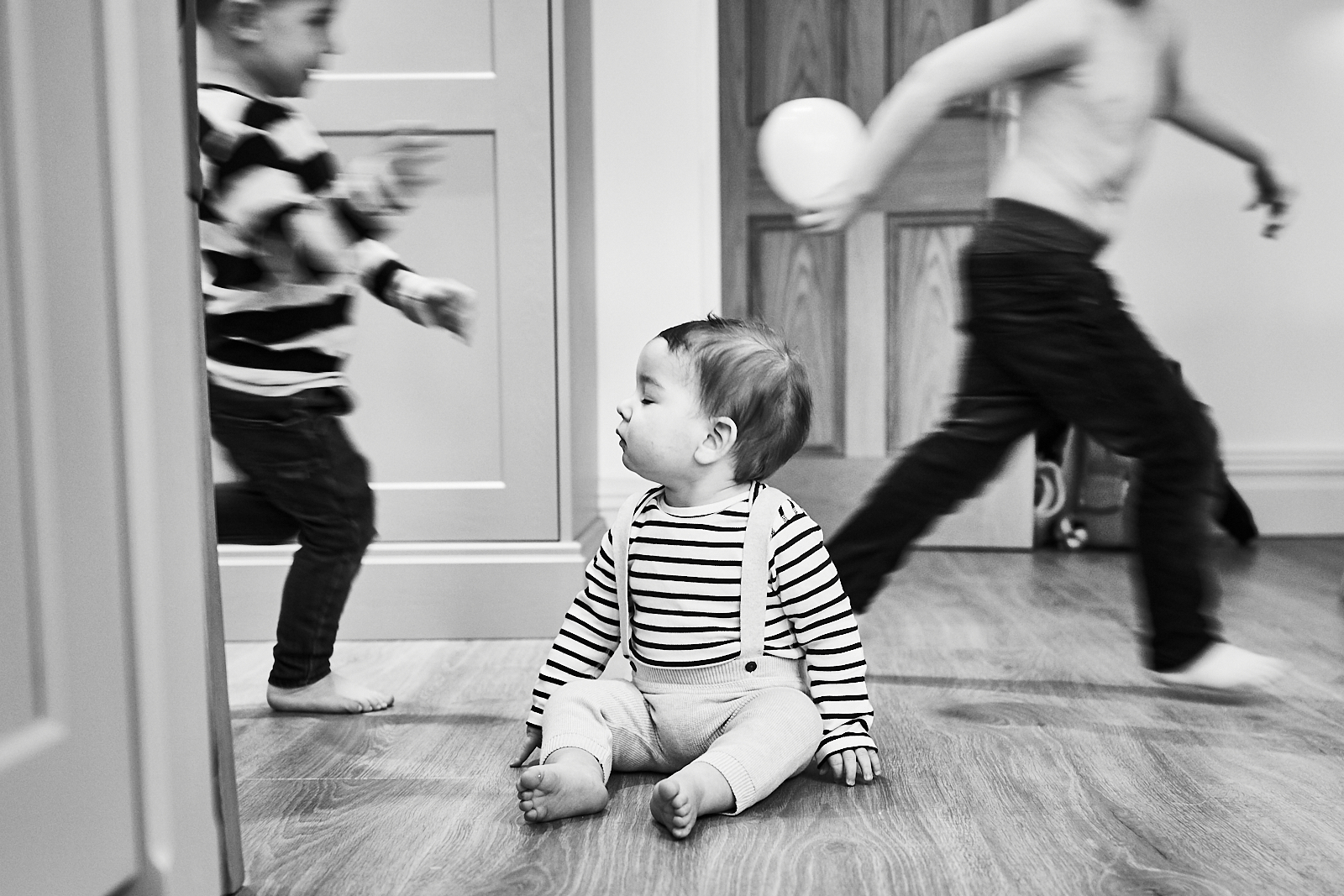 fun photo of family life with boys running at home