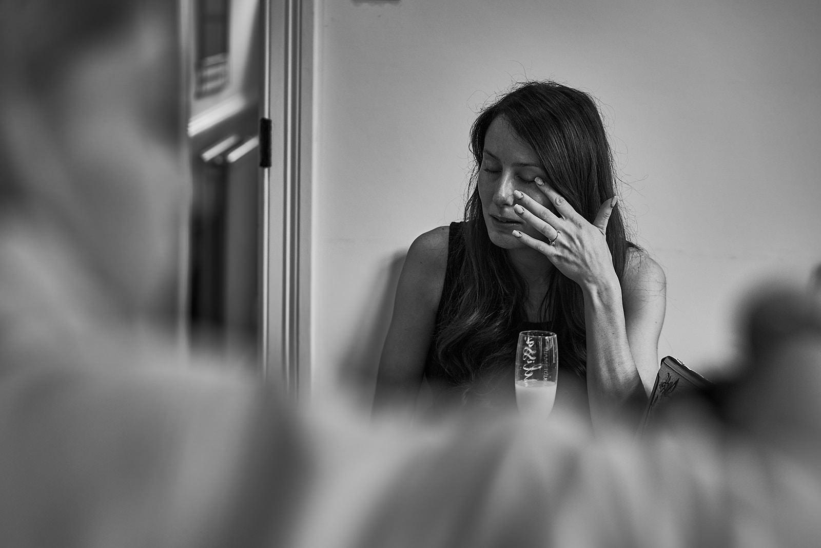 candid photo of bridesmaid wiping away tear at wedding