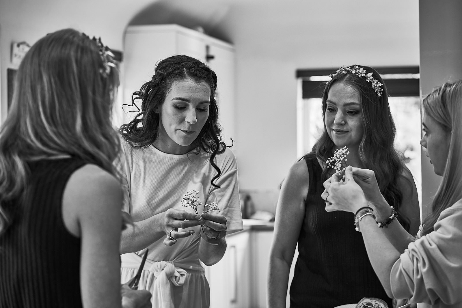 bride with bridesmaids chatting about hair flowers