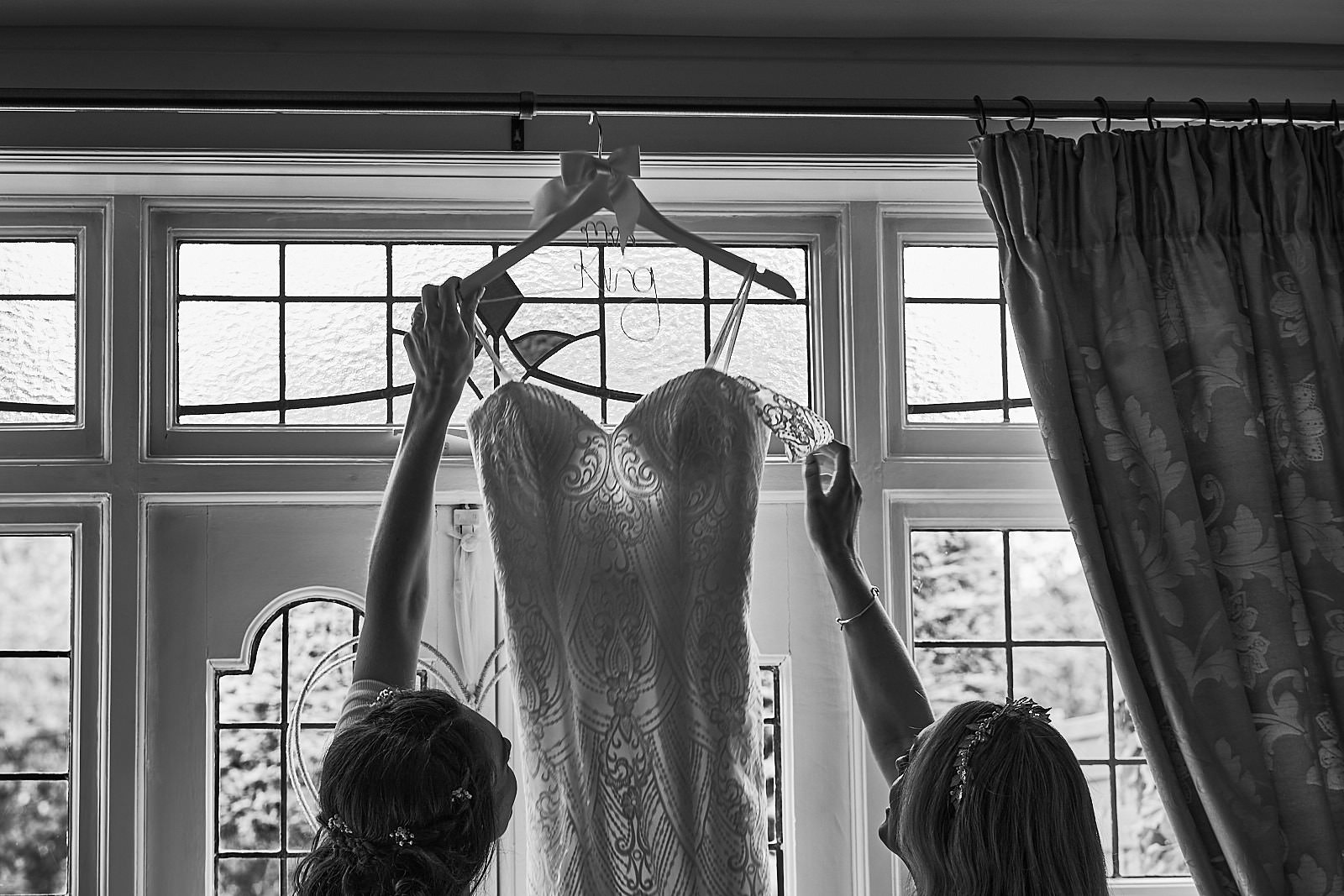 black and white photo of bride and sister reach for the wedding dress