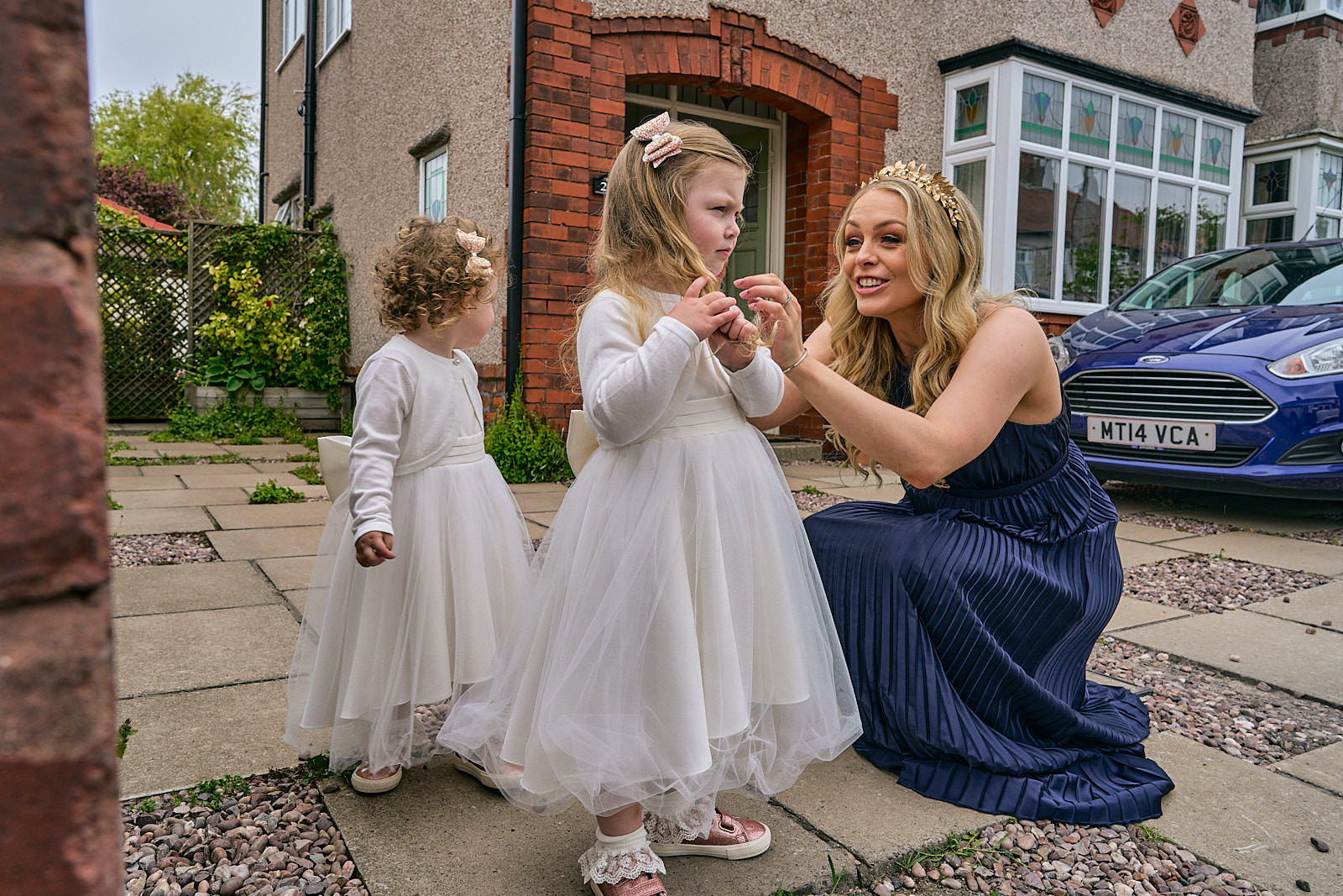 bridesmaid smiles at flowergirl outside home in crosby