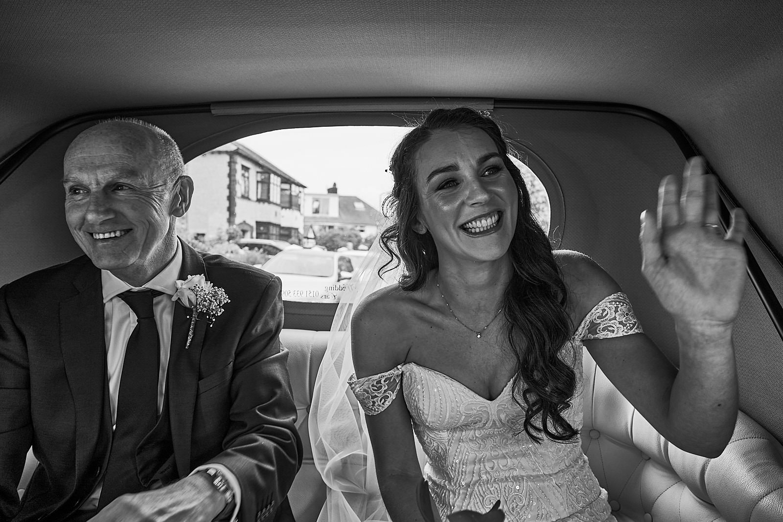 bride waves in the back of her wedding car
