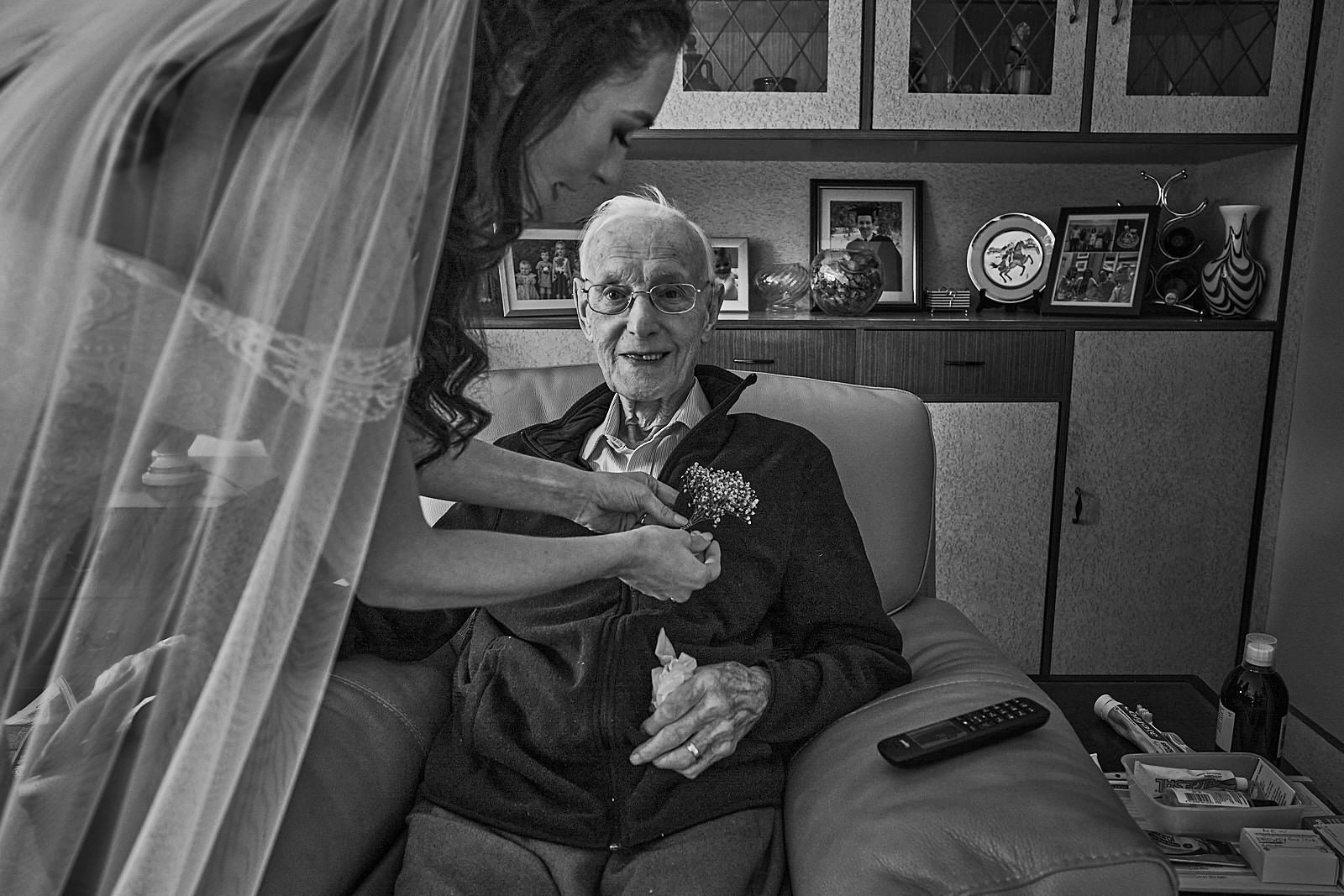 bride puts button hole on grandad who can't make the wedding