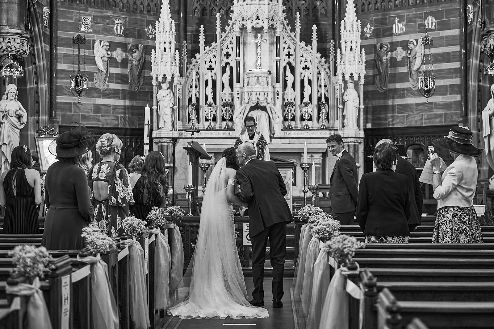 black and white candid photo of dad kissing bride in church