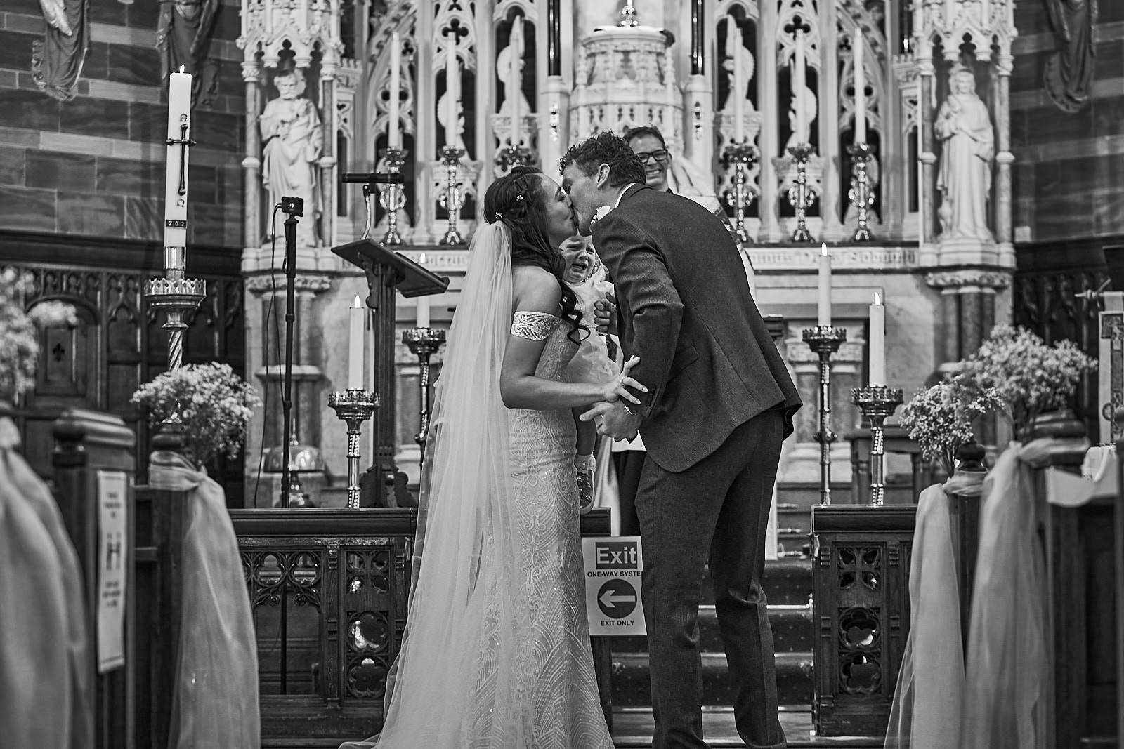 natural black and white photograph of couple kissing during ceremony