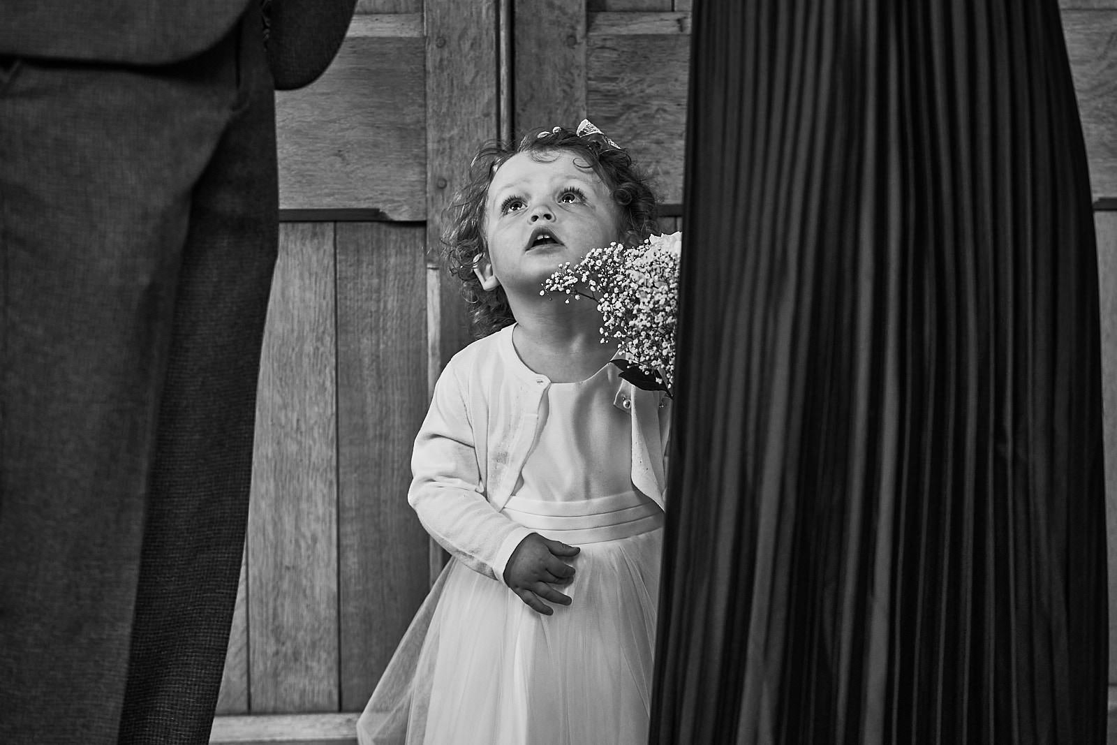 flower girl looks tiny as she looks up at guests during wedding
