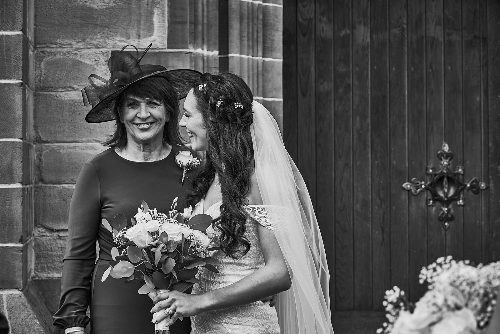 natural moment of mum and bride laughing outside church
