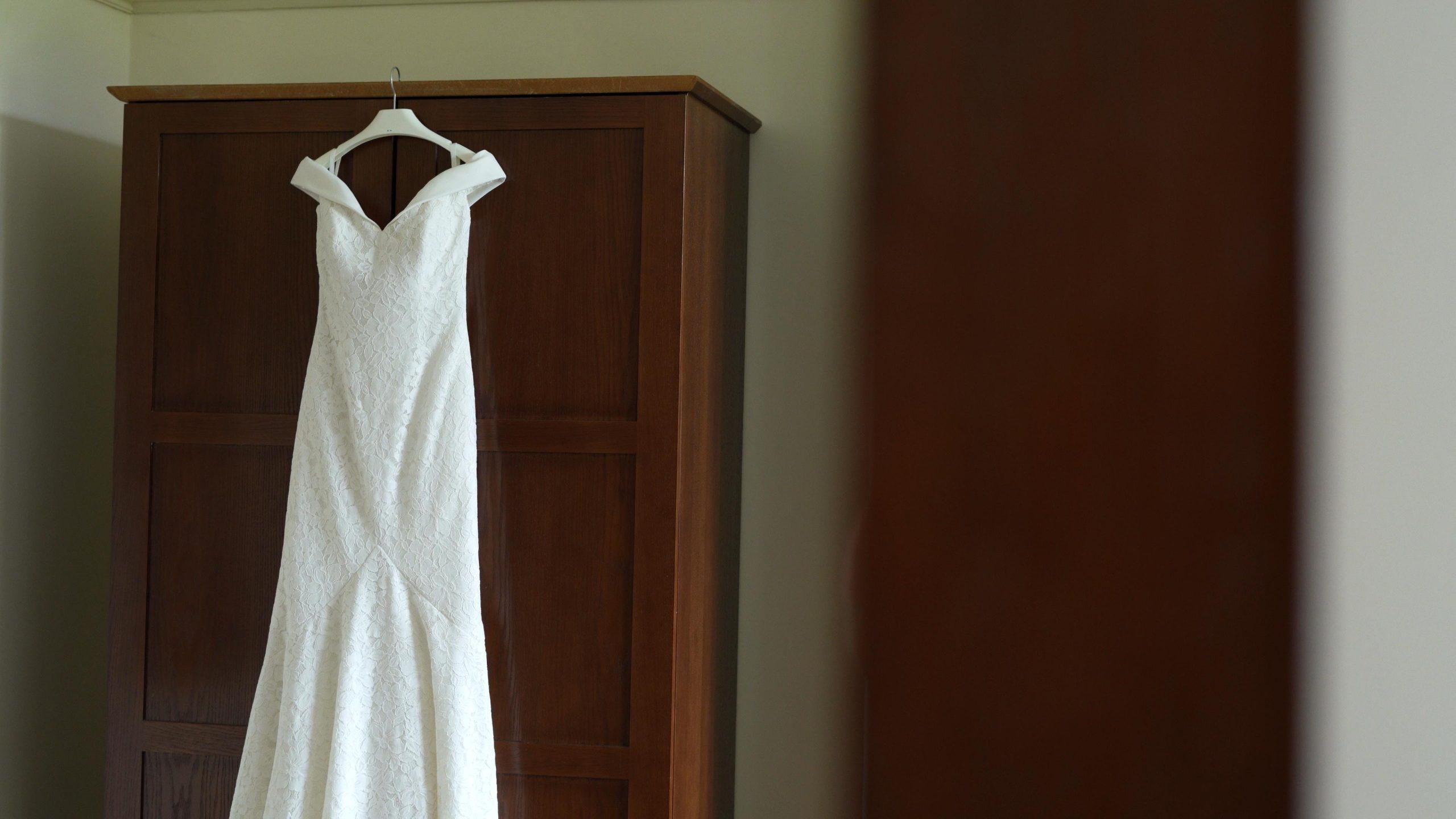 off shoulder wedding dress hangs on wardrobe