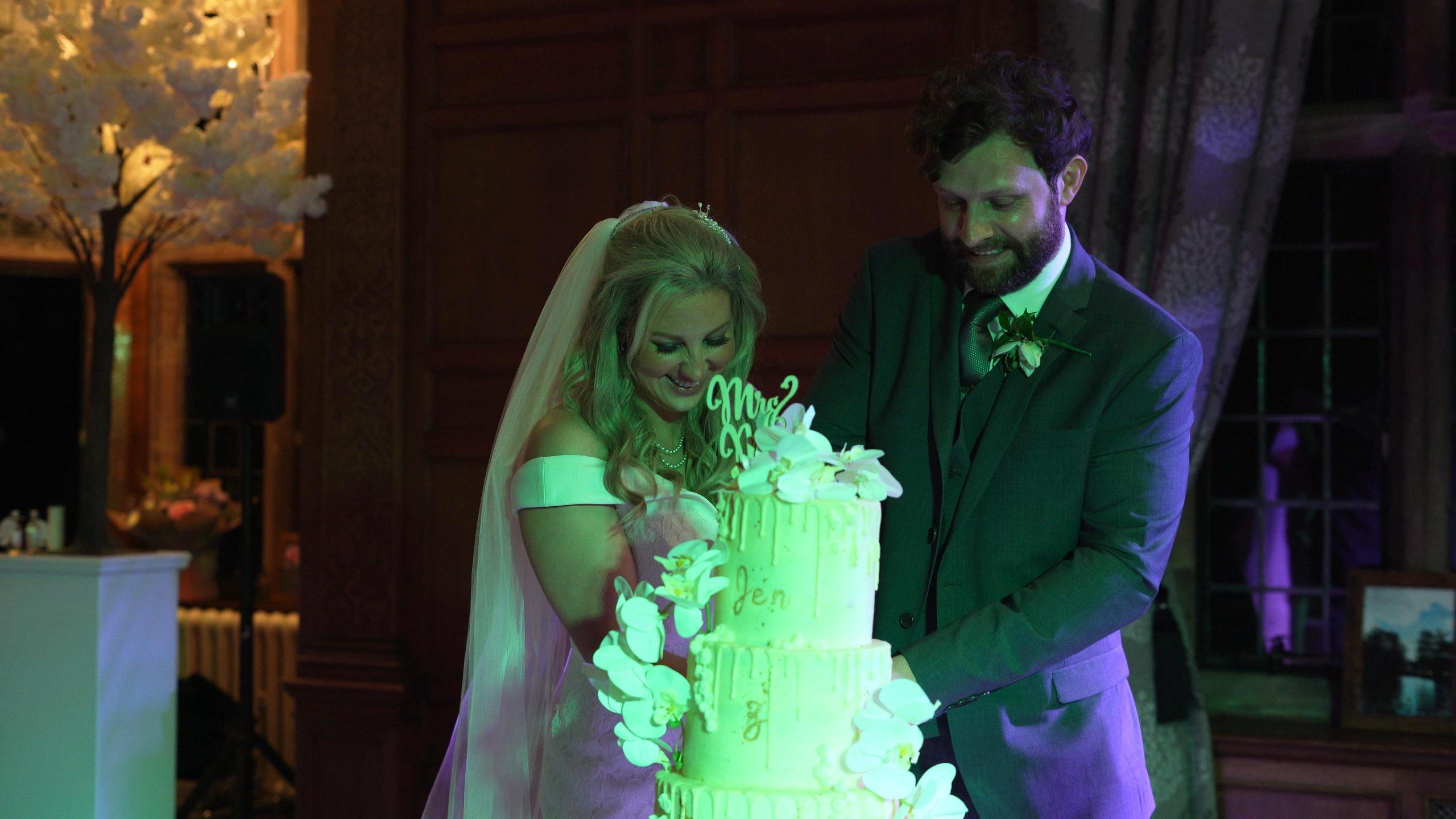 couple cut wedding cake at inglewood manor