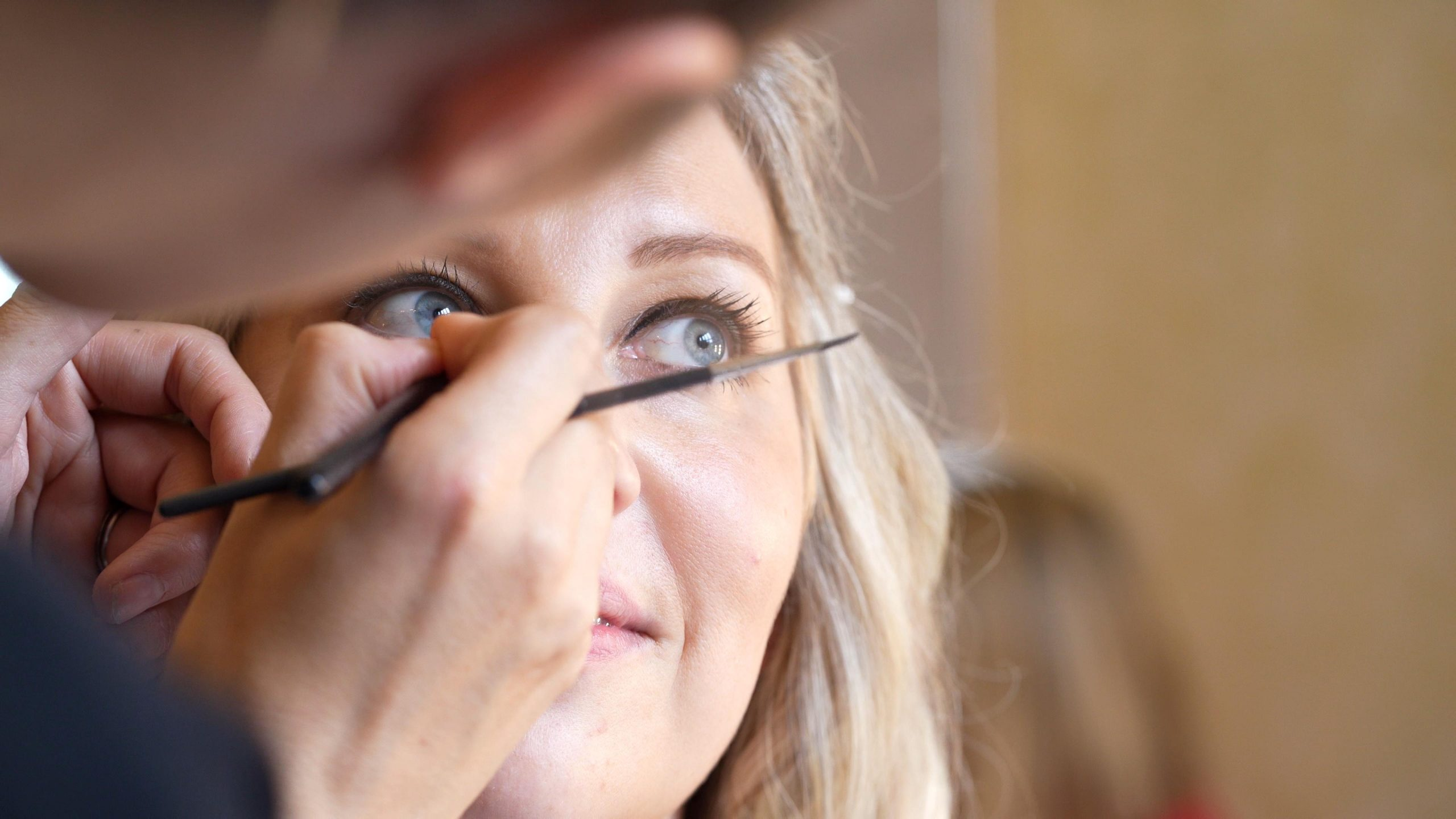 bride has her eye makeup touched up during wedding