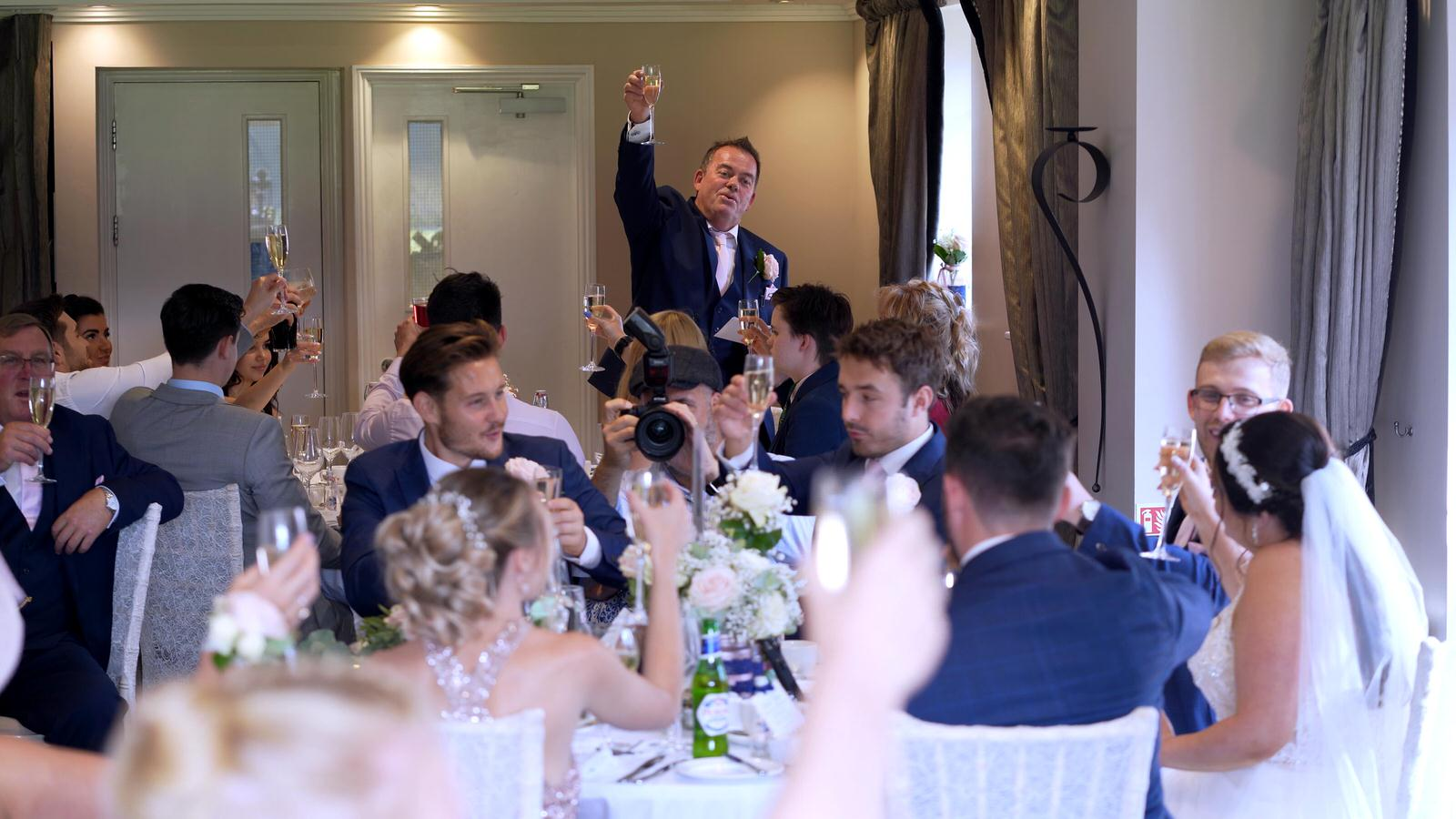 father of the bride raises a toast during speeches