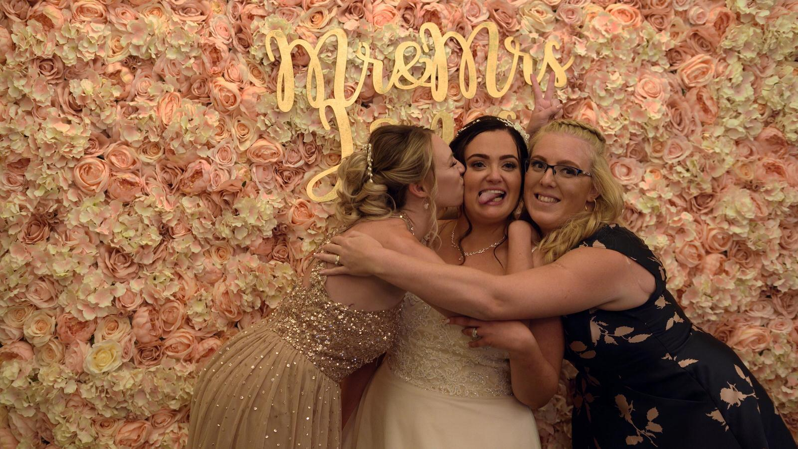 bride poses with friends for photobooth