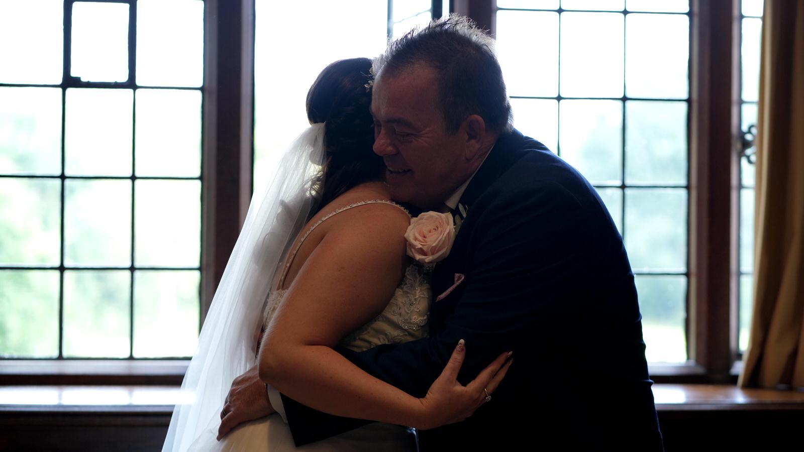 dad hugs bride in front of bright window