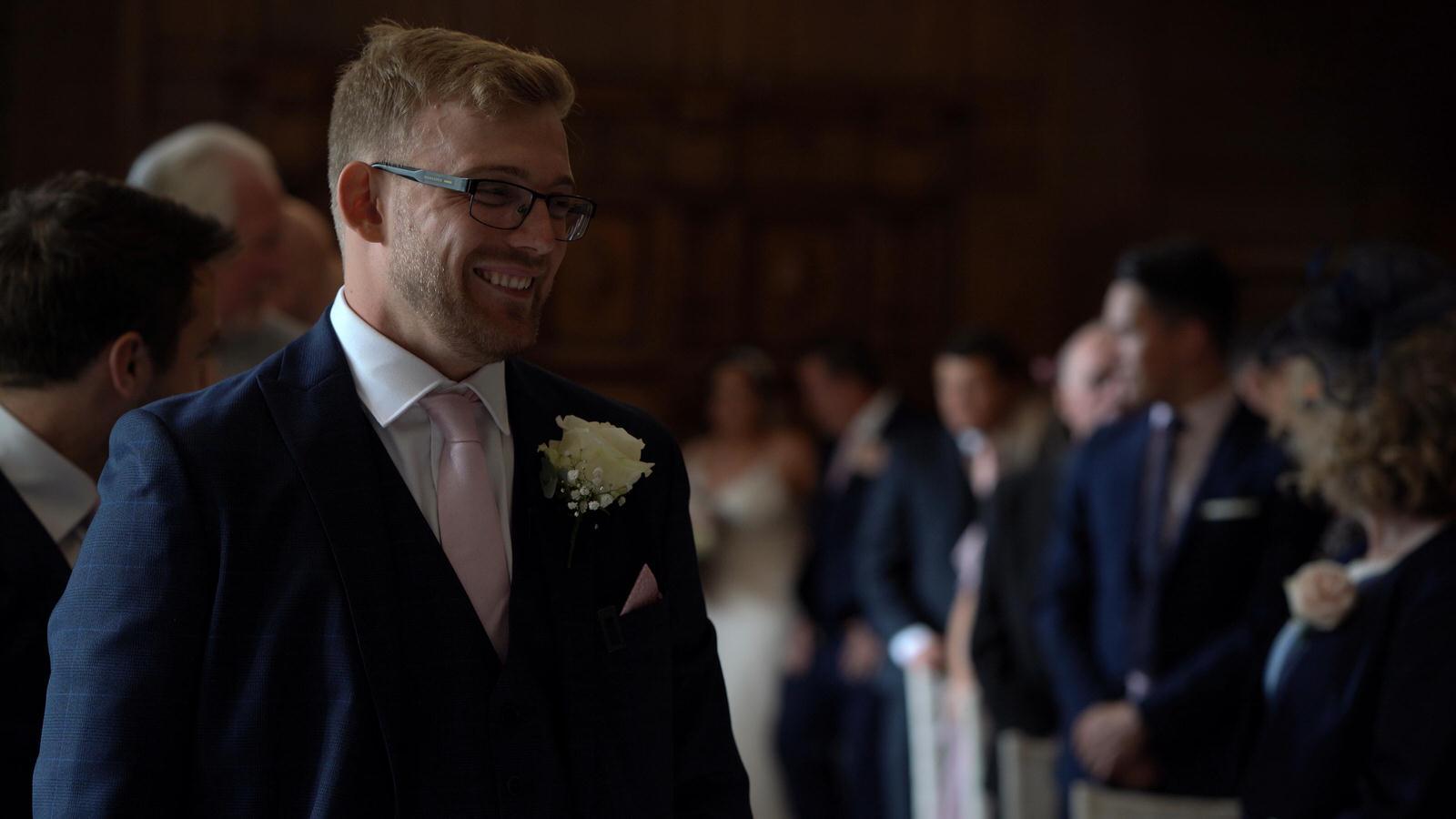groom smiles as he waits for bride to walk down aisle