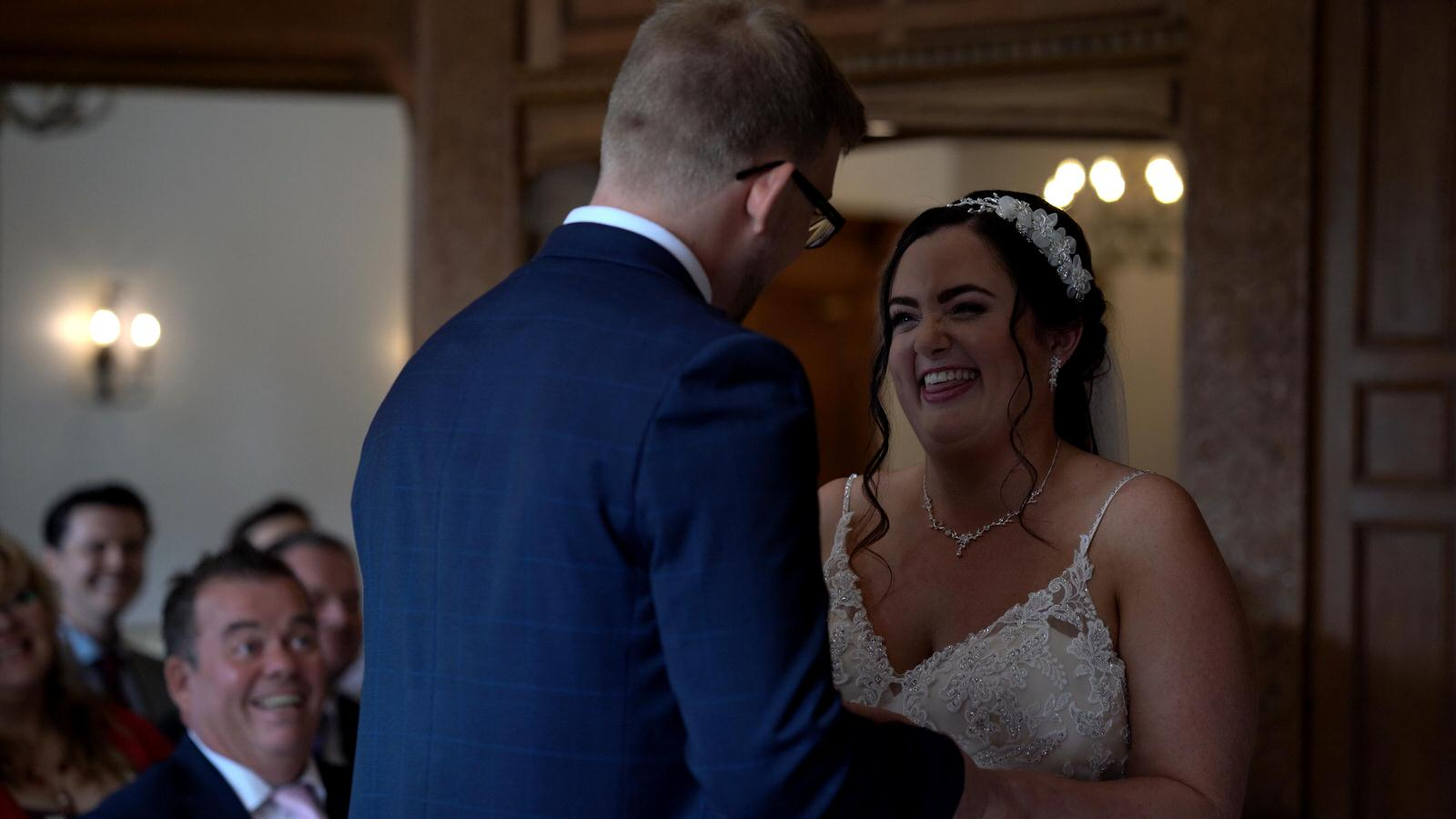 bride and groom laugh with each other during ceremony