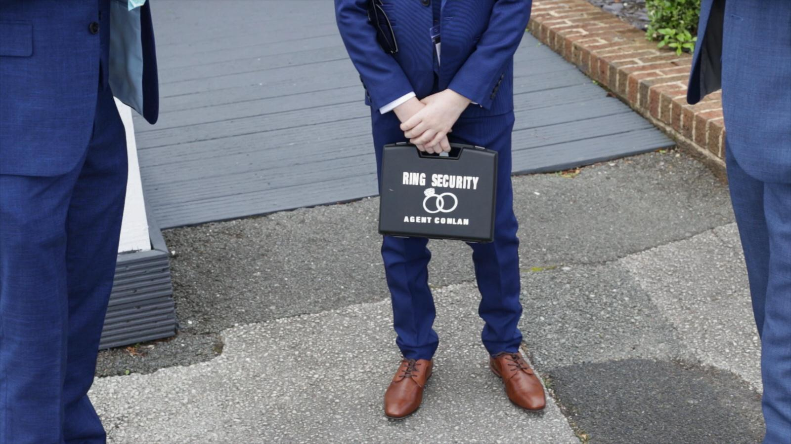 page boy holds wedding ring security box