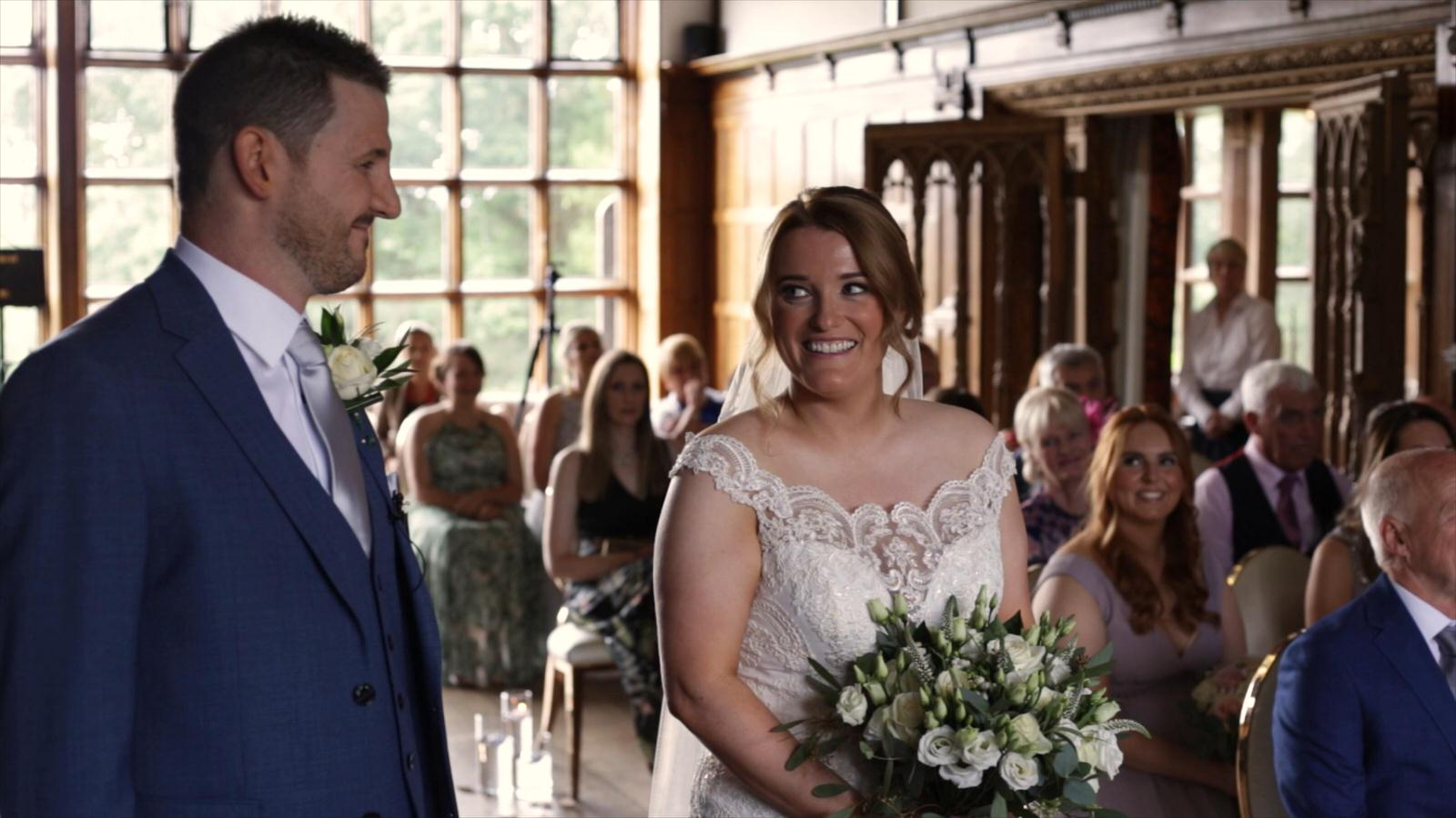 bride smiles at groom during wedding ceremony at Hillbark hotel