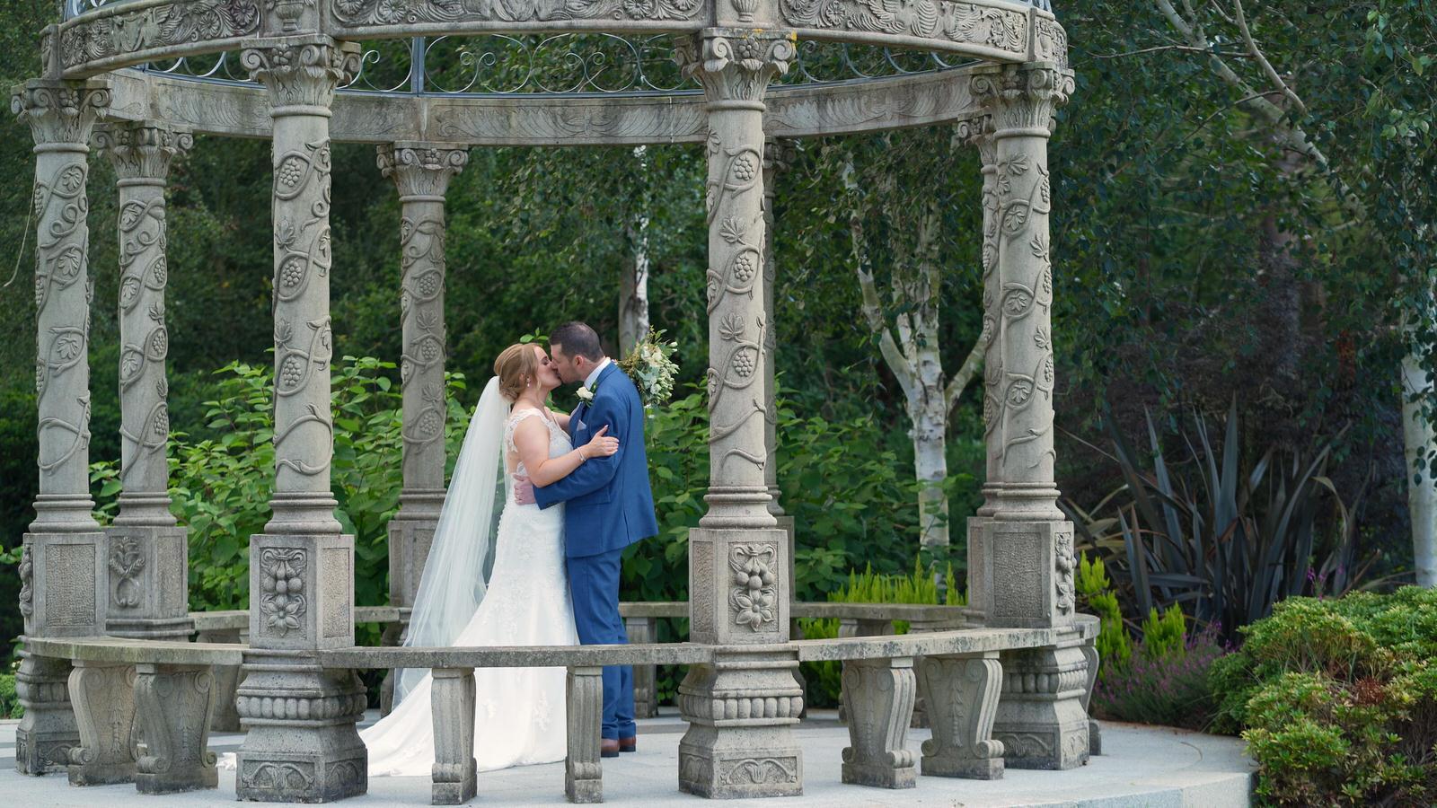 bride and groom kiss under pagoda outside Hillbark Hotel