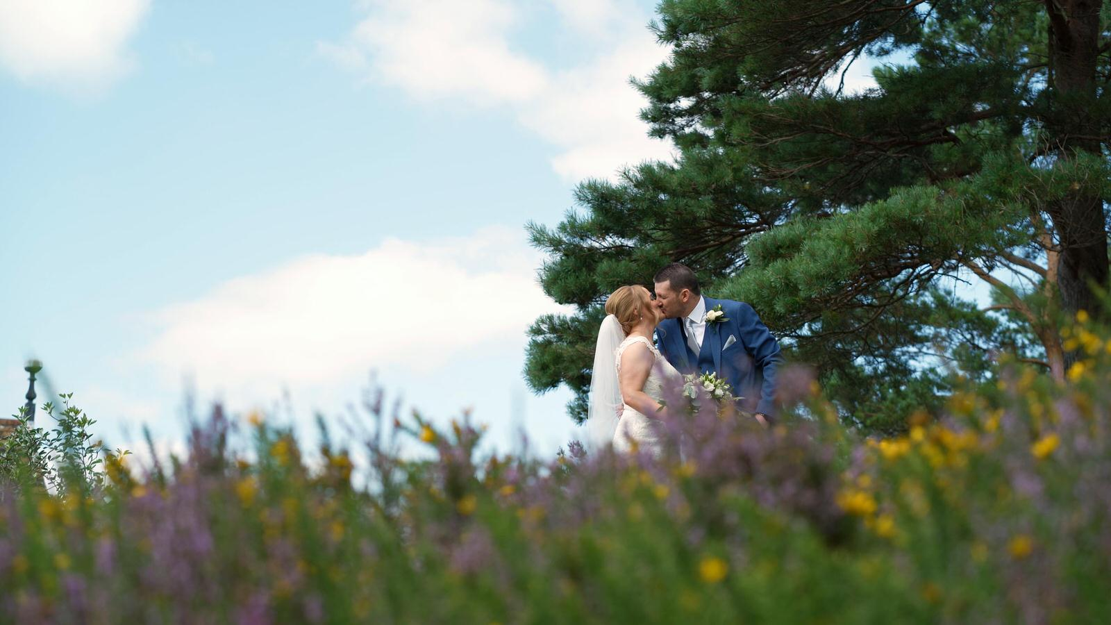 newlywed couple in long grass outside hillbark hotel