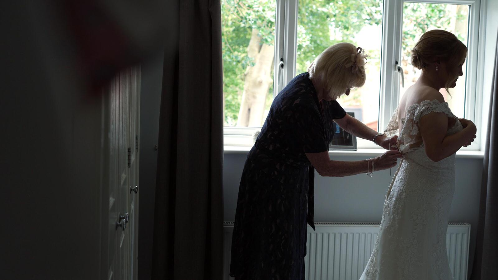videographer films bride getting help in to her wedding dress