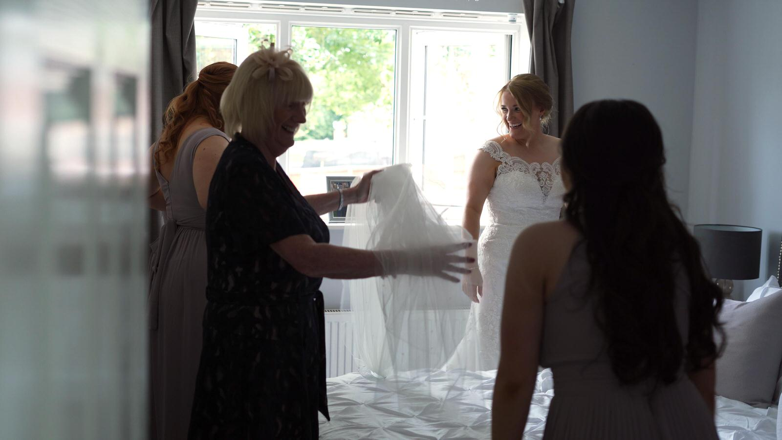 bride smiles at bridesmaids waiting for her veil