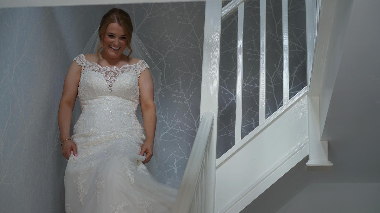 bride in wedding dress walks down stairs at home